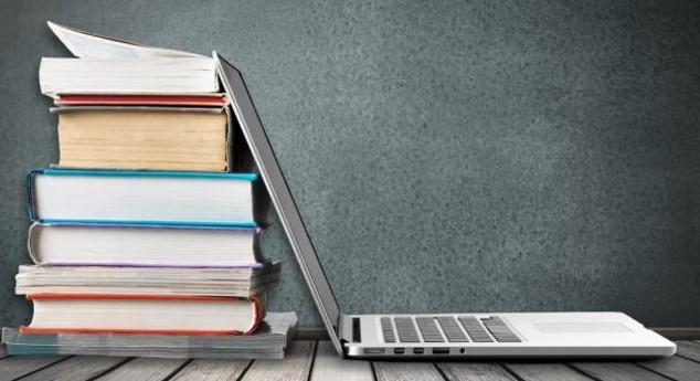 estudio ordenado, portatil apoyado sobre pila de libros