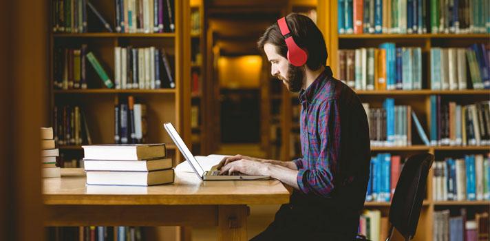 chico estudiando en una biblioteca