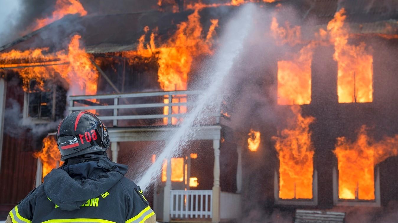 Trabajo de Bombero: bombero extinguiendo el fuego de una vivienda
