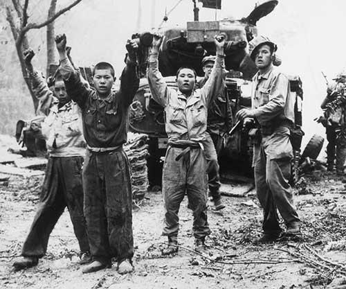 un soldado apunta a tres niños que tienen los brazos alzados